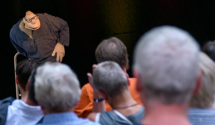 """Die erste Open-Air Veranstaltung des Savoy Kino Vereins war in vielerlei Hinsicht eine bemerkenswerte Veranstaltung. Werner Momsen, alias Detlef Wutschik, trat auf einer kleinen Bühne auf dem Schulhof der Bordesholmer Lindenschule vor 54 Zuschauern auf. Zuschauer kamen aus Kiel, Neumünster und aus dem Kreis Rendsburg-Eckernförde und waren von dem Ambiente des Schulhofes und vor allem von der Darbietung """"Werner Momsens"""" begeistert. Der vielseitig interessierte Werner Momsen hatte in den letzten Wochen viel Zeit, sich von tagesaktuellen und auch nicht so im Rampenlicht des allgemeinen Interesses liegenden Dingen eine feste Meinung zu bilden, die er mit großer Überzeugung, überraschenden gedanklichen Verknüpfungen und natürlich mit sehr viel Humor vortrug. Solch eine tolle Open-Air-Veranstaltung kann es gerne öfter geben."""